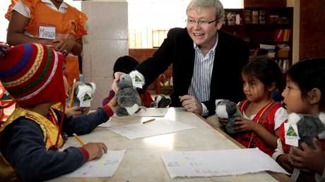 """Then Prime Minister Kevin Rudd giving out toy koalas to children in Lima, Peru in 2008 while attending the meeting of regional leaders called the APEC Summit. Using gifts and being friendly and jokey to try to charm another country's leaders to do what you want instead of being tough is an Australianism called """"koala diplomacy""""."""