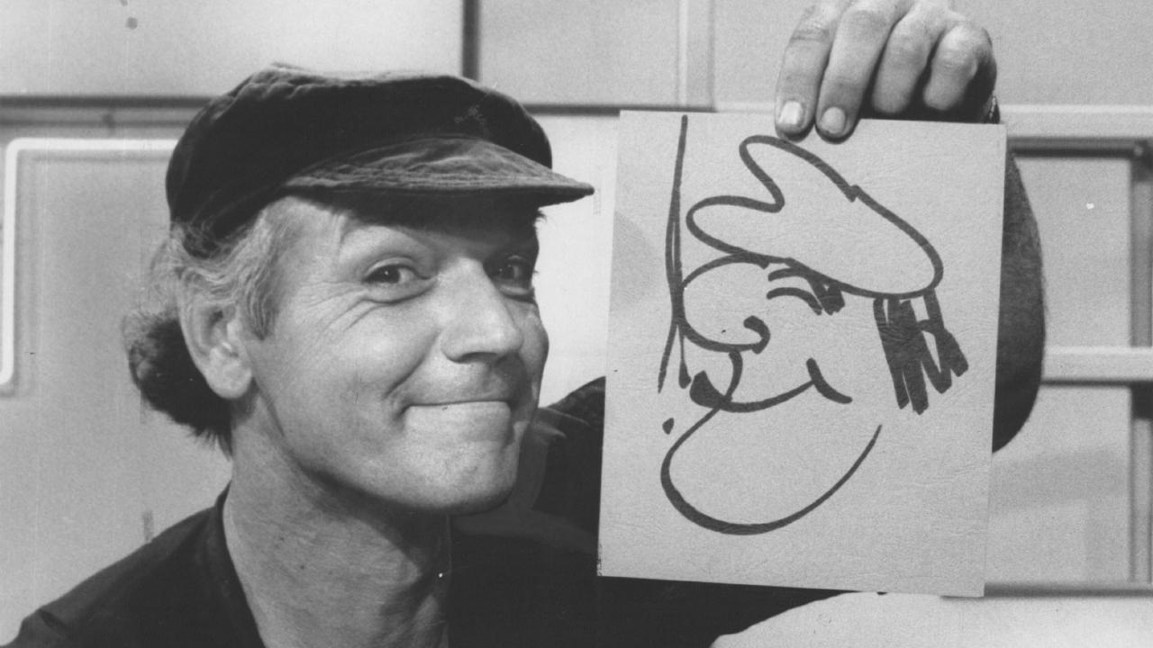 Larry Pickering with one of his cartoons.