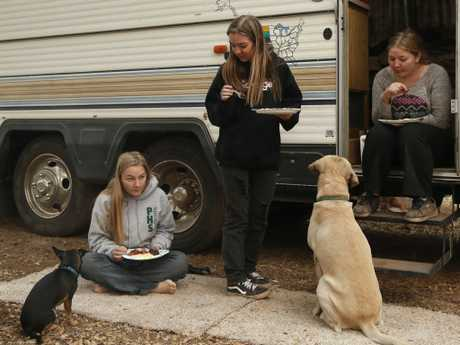 Sisters Arissa Harvey, from left, Araya Cipollini, and Arianne Harvey with their dogs at the motor home they've bee living in since their home was destroyed. Picture: AP