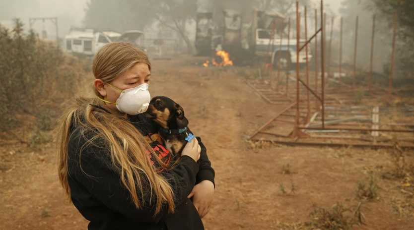 Arianne Harvey holds her dog TJ near where her home was destroyed in Paradise, California. Picture: AP