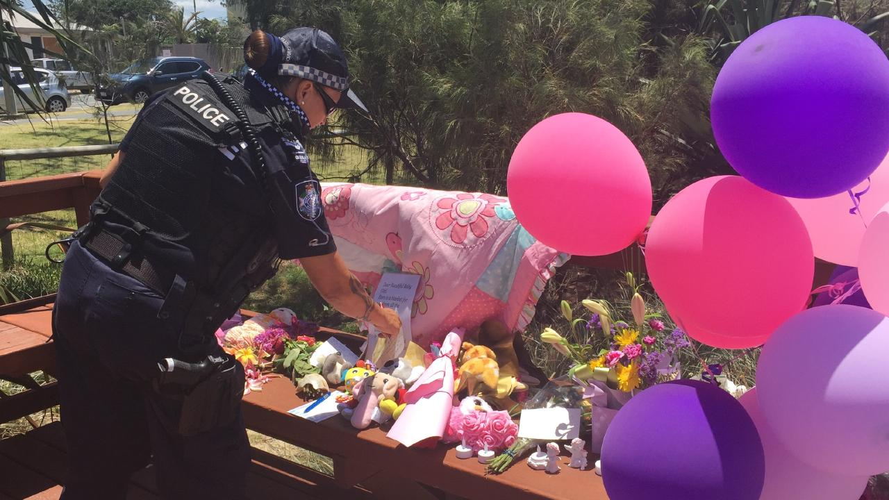 Police officers wipe away tears as they bring toys and pay their respects near where the baby girl was found dead. Picture: Tali Eley.