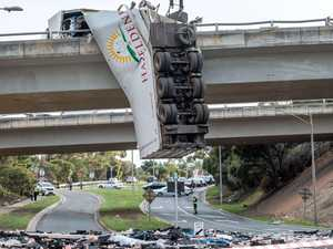 Truck rolls over, hangs off freeway ramp