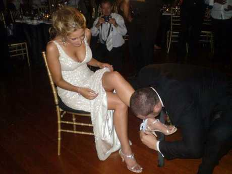 The loved-up groom removes the garter from the bride's leg.
