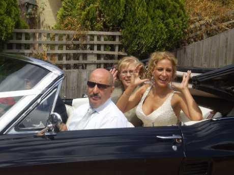 Renata beams happiness in her classy convertible car.