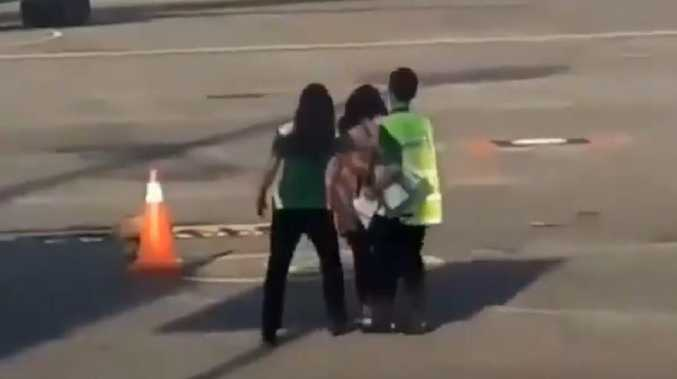 The woman is held back as she tries to make a dash for her Citilink flight. Picture: @goenrock