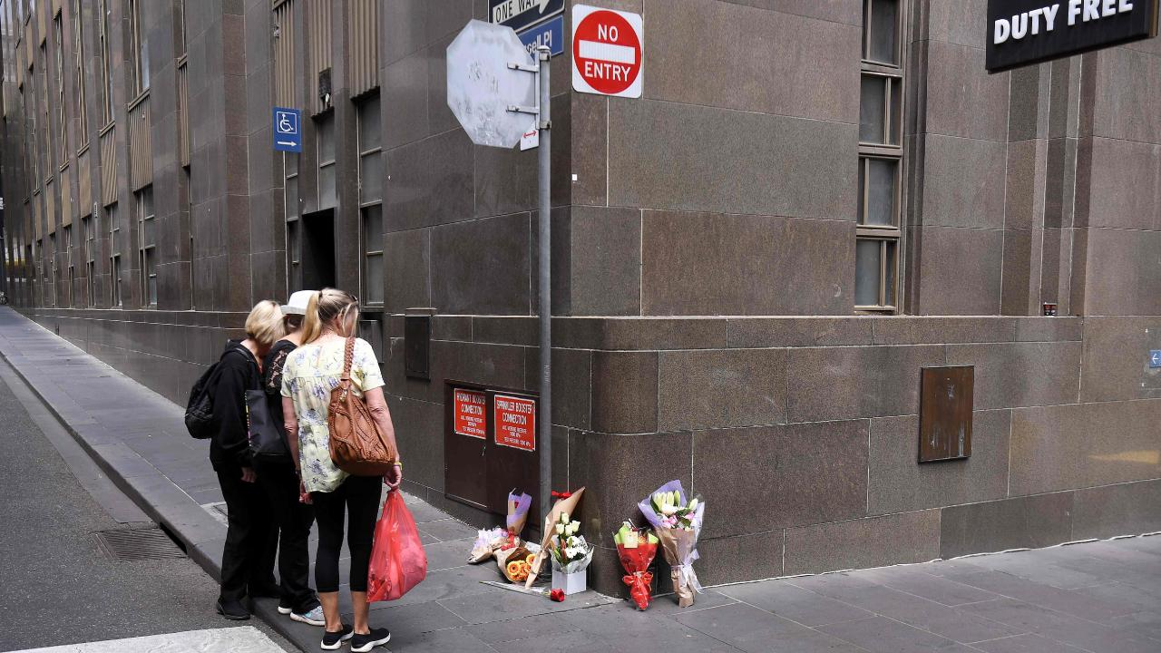 People look at flowers left at the scene where a man was killed in the November 9 knife rampage carried out by an Islamic extremist. Picture: William West/AFP
