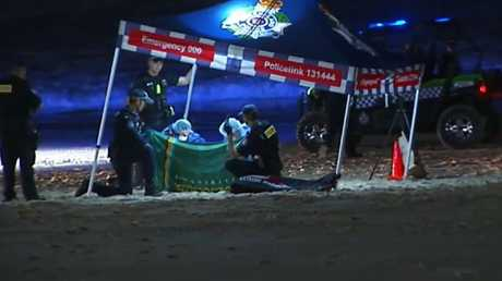 Police at the crime scene set up on the beach in the early hours of Monday morning. MUST Picture: 9NEWS