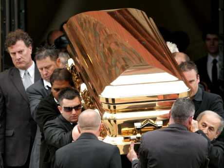 The gold coffin with the body of gangland killer Carl Williams leaves the funeral service at a church in Essendon. Picture: Stuart McEvoy