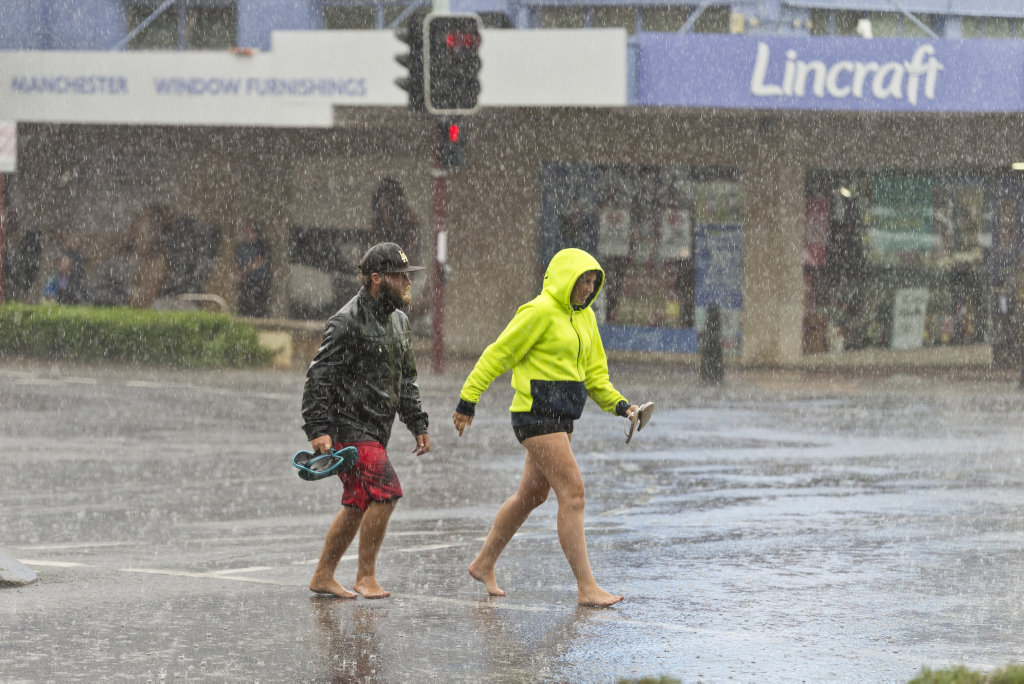 Toby More and Amy Walters scramble across Ruthven St as rain falls in the Toowoomba CBD.
