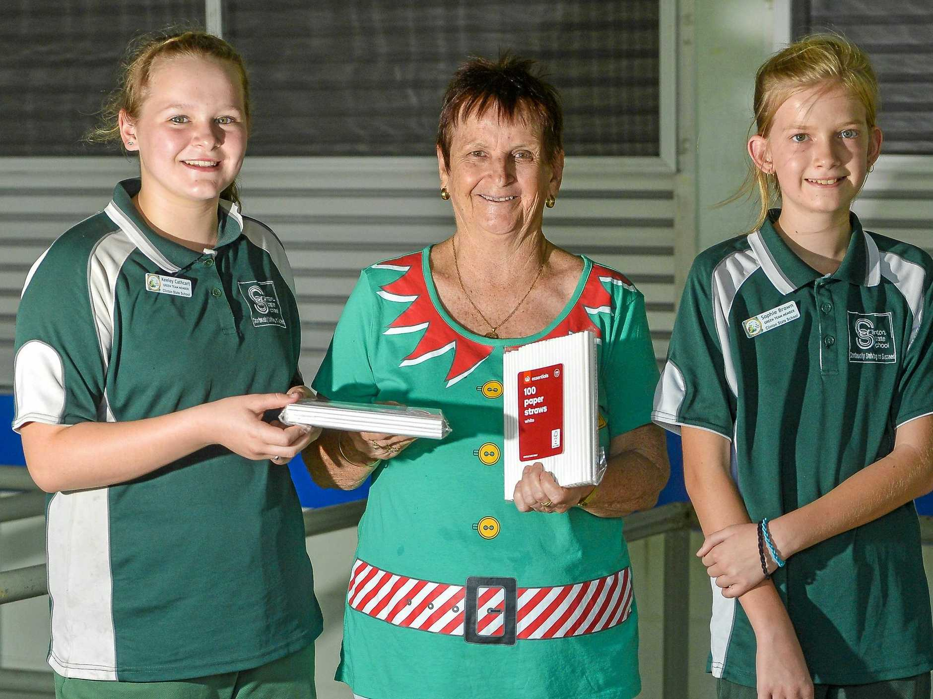Clinton State School students Keeley Cathcart and Sophie Brown with tuckshop convenor Gail Molloy are recycling single-use plastic straws to make way for environmentally friendly paper straws.