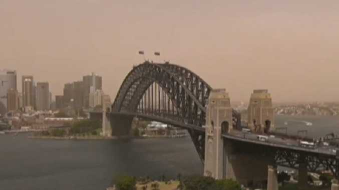 Sydney Harbour takes on a reddish tinge about 11.30am. Picture: Channel 7