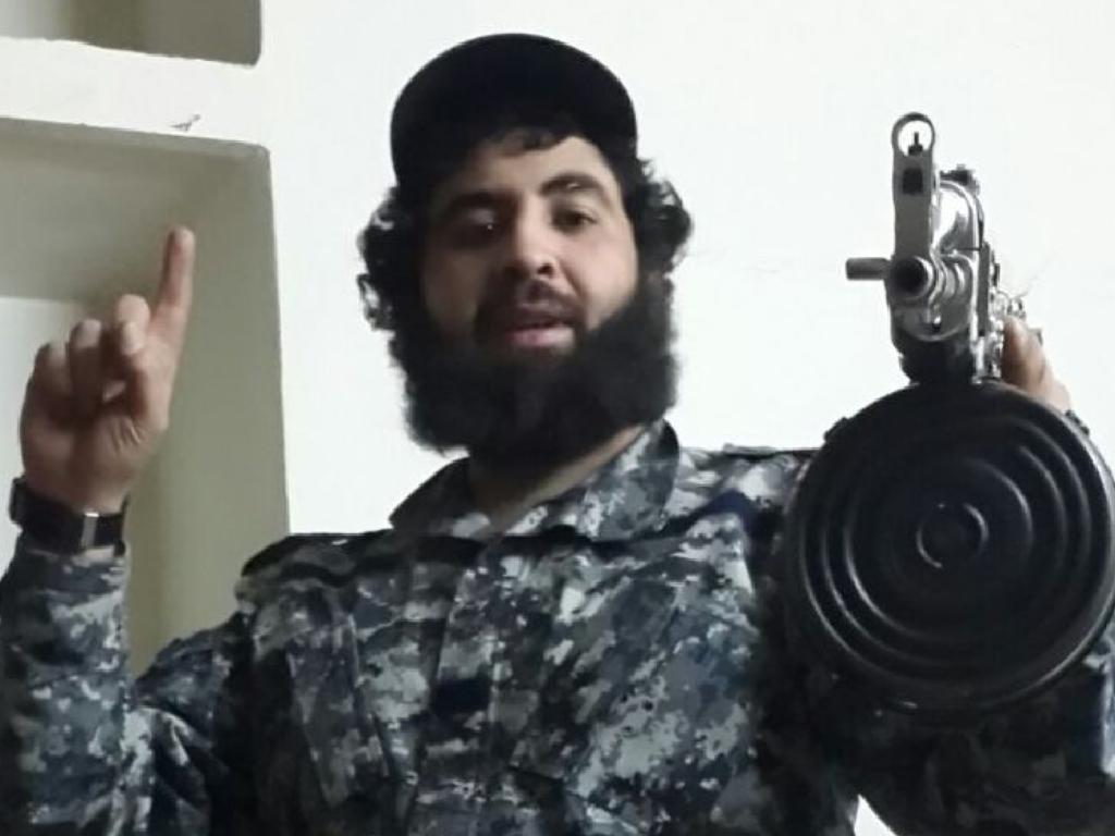 Clad in military fatigues, Sydney man Ahmed Merhi holds a large assault rifle while posing for a photo.
