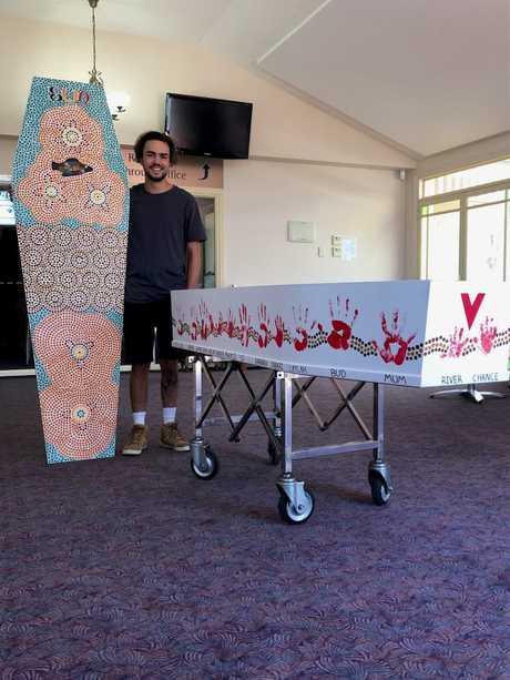 Aboriginal artist Kane Brunjes with Ashley Boney's coffin adorned with Aboriginal artwork.