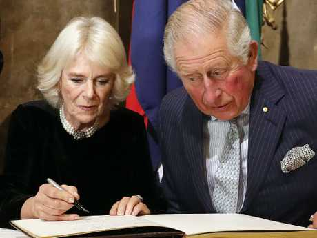 Camilla, the Duchess of Cornwall, and Prince Charles sign the guest book as they visit Australia House. Picture: AP