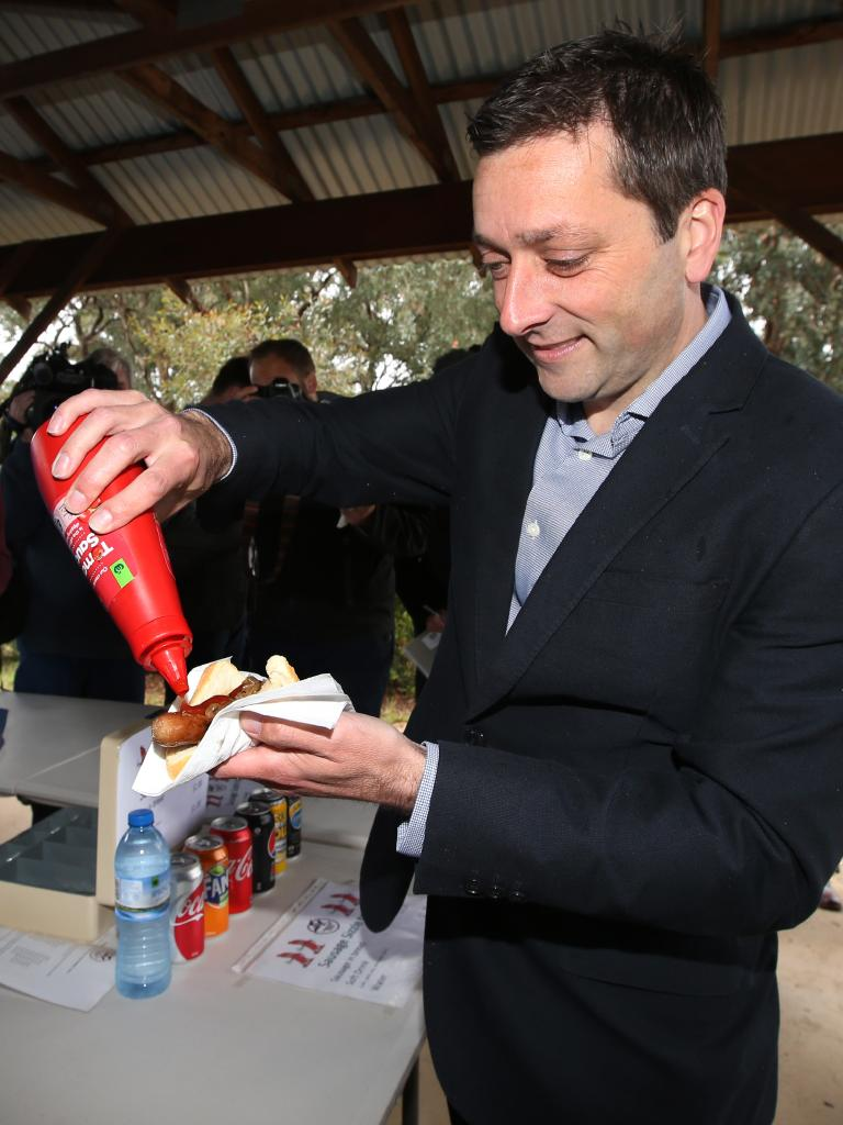 Opposition leader Matthew Guy sauces up a poll day hot dog. Picture: David Caird.