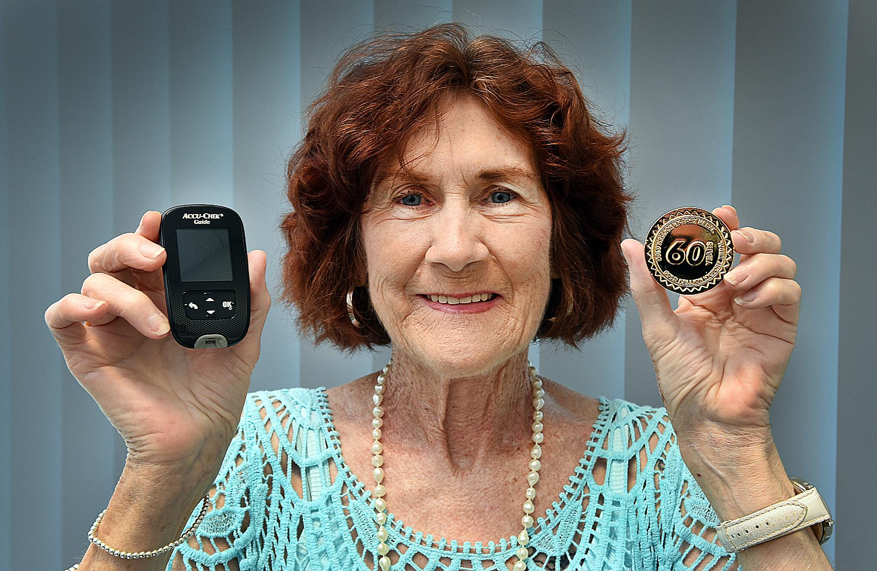 HEALTHY LIFE: Hervey Bay's Beryl Lethlean has been living with diabetes for 60 years, here she holds her glucometer which measures blood sugar levels and her Kellion Victory Medal.