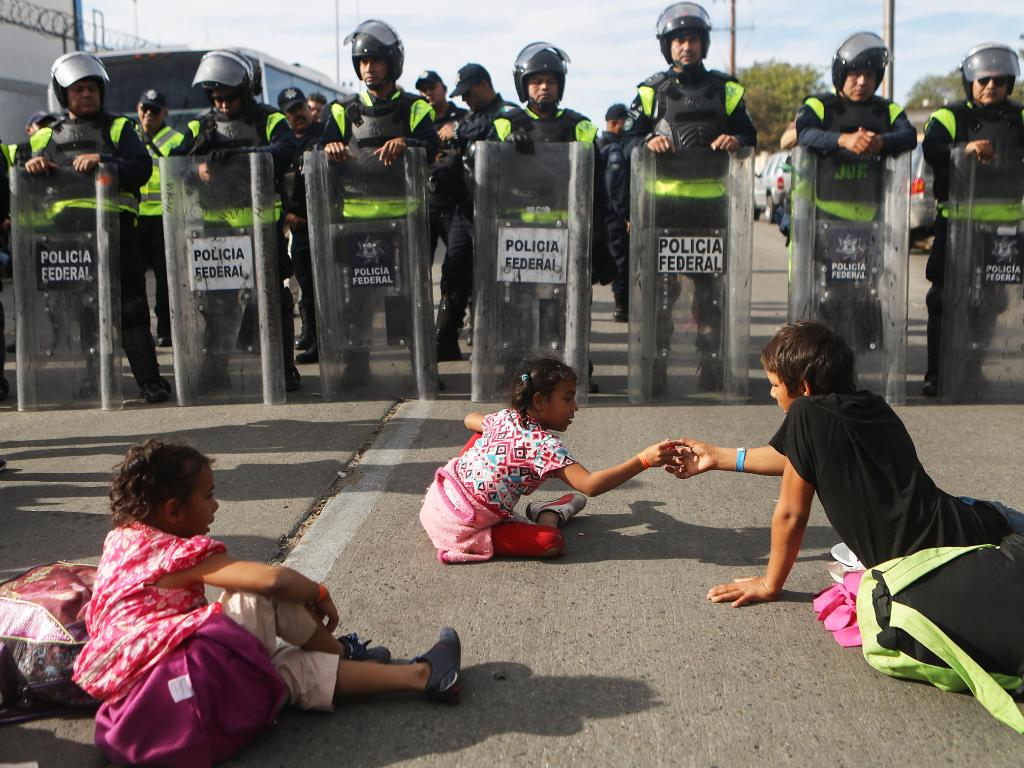 Versus how migrants spent their Thanksgiving — sitting in front of Mexican riot police outside the El Chaparral port of entry. Picture: Getty