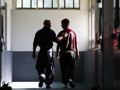 A juvenile detention guard walks with a teenager. Picture: Tim Hunter.