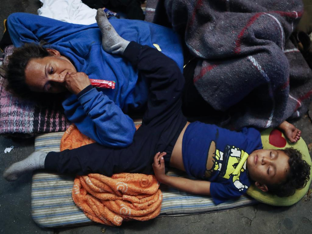 Honduran child migrant Daniel Bonilla II sleeps next to his mother Rosa on the street outside an overcrowded temporary shelter set up for members of the 'migrant caravan'. Picture: Getty