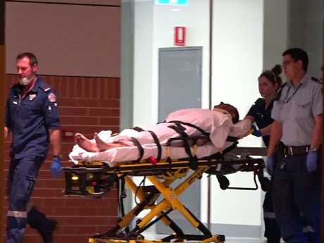A man strapped on a gurney is taken to hospital after the alleged attack eleven days ago.