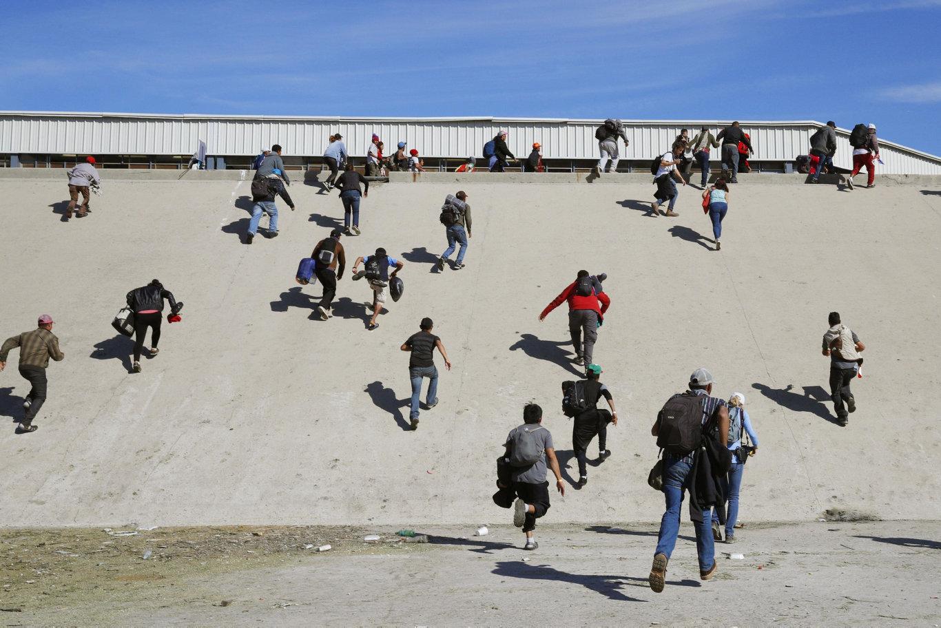 Migrants from Central America climb a steep embankment in Tijuana, Mexico, toward the U.S. border checkpoint.