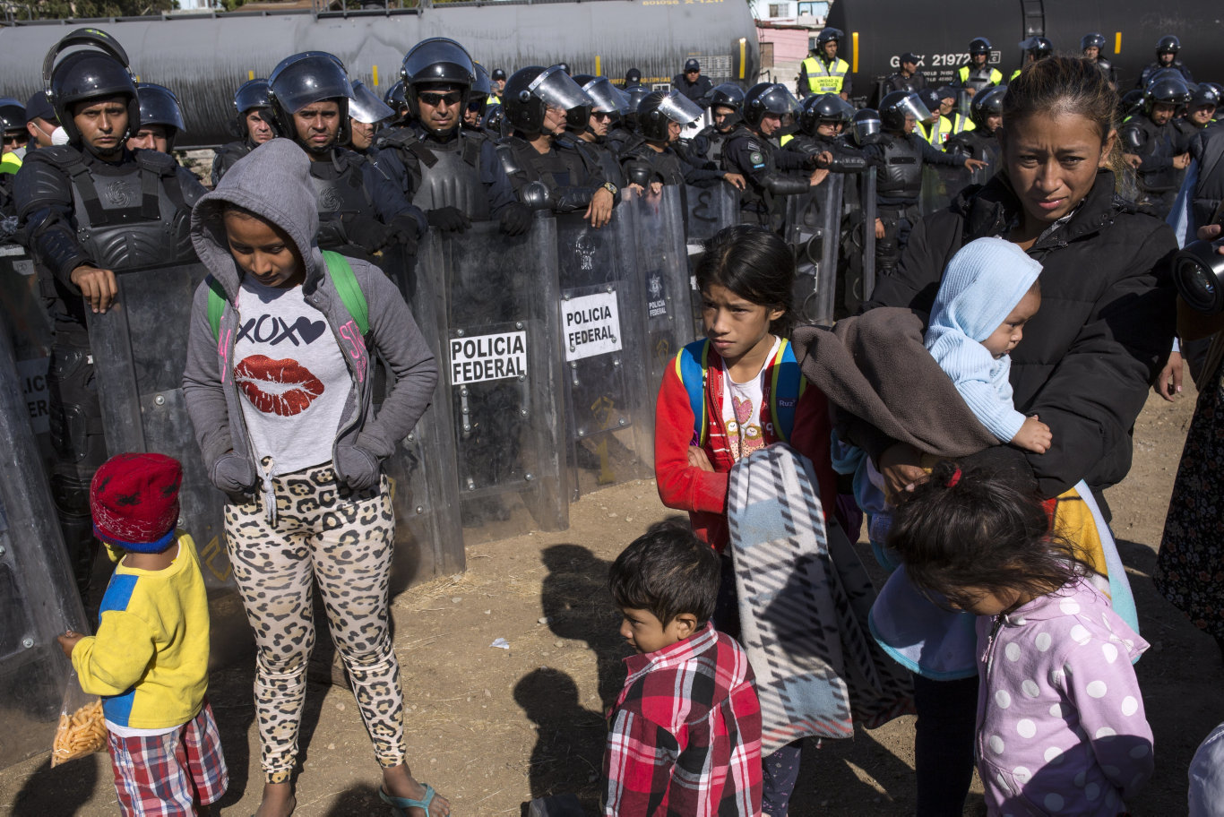 Migrants stand near Mexican police at the Mexico-U.S. border in Tijuana, Mexico as they try to reach the US. The mayor of Tijuana has declared a humanitarian crisis in his border city and says that he has asked the United Nations for aid to deal with about 5000 Central American migrants who have arrived in the city.