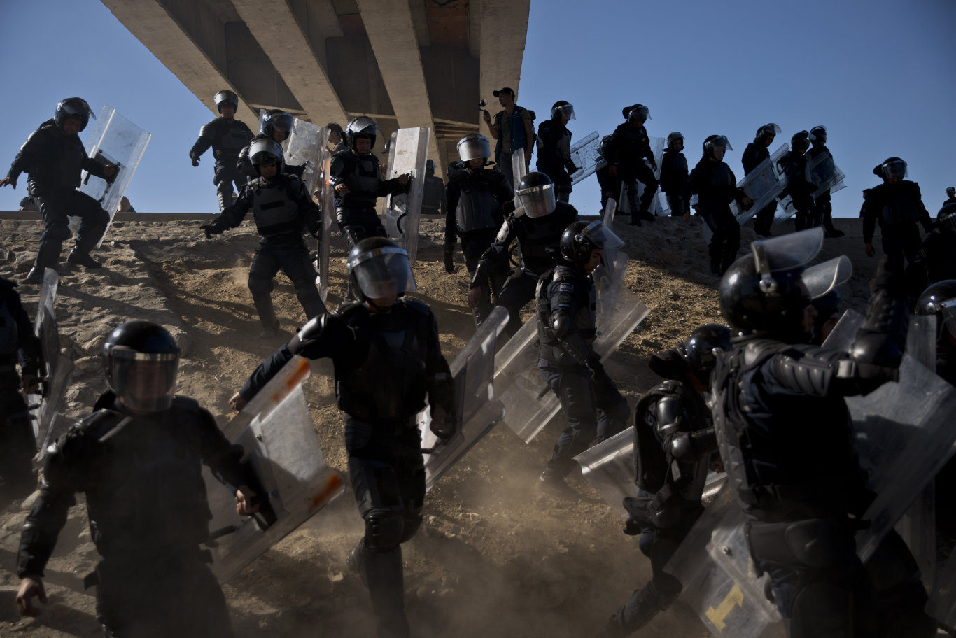 Mexican police run as they try to keep migrants from getting past the Chaparral border crossing in Tijuana, Mexico, near San Ysidro, California.