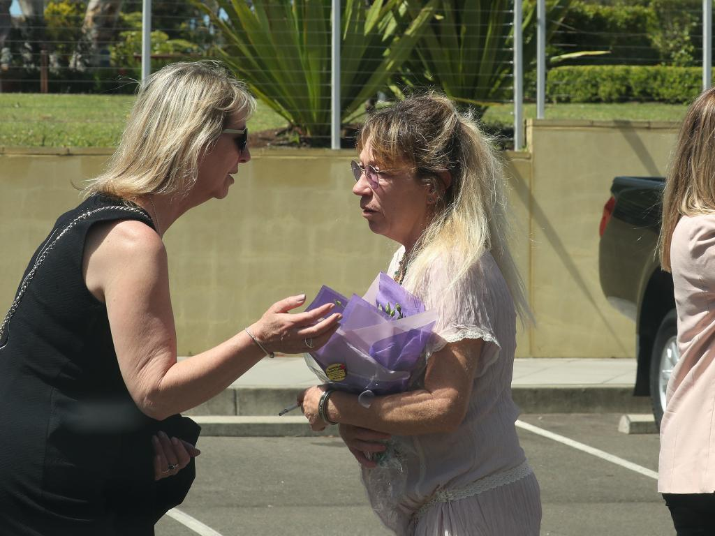 Lindy Anderson being comforted by a friend at her son's funeral.