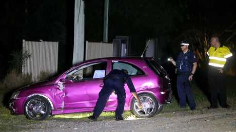 Police inspect the car believed to be involved in the shooting incident at a property in Pimpama. Photo: Regi Varghese