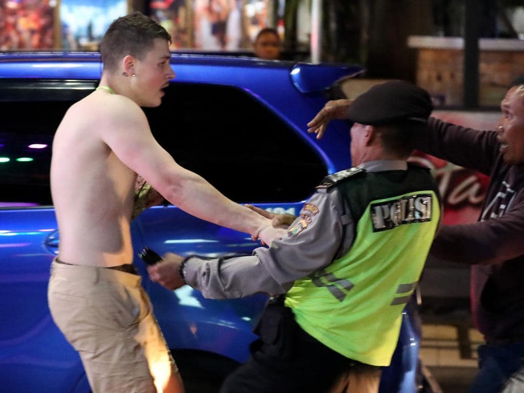 A young Australian man pushes a policeman in Kut. Picture: Liam Kidston.