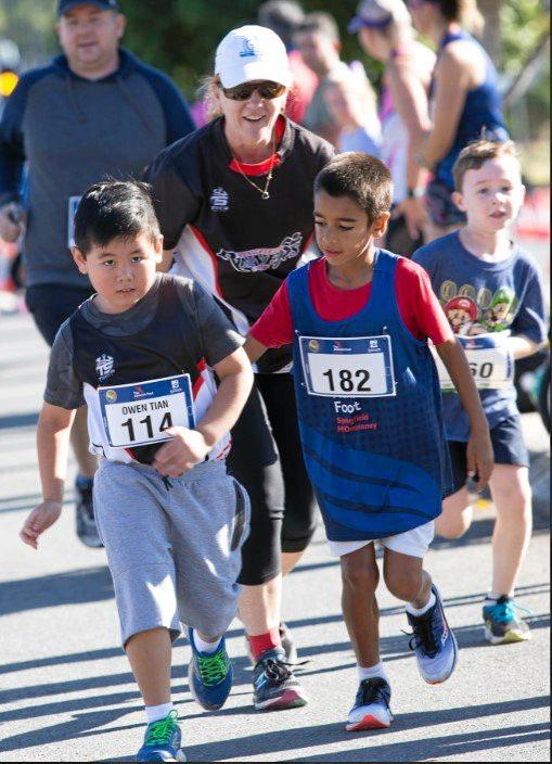 HELPING HAND: Joshua Williams (right) shows terrific spirit by helping another competitor to the finish line.