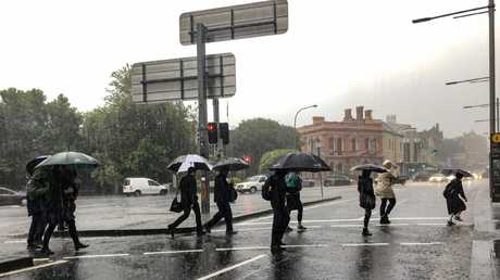 Commuters struggled against torrential rain and gale force winds in Newtown as Sydney is lashed with a monumental early summer storm. Picture: Nicholas Eager