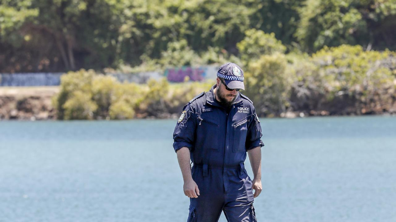NSW Police Public Order and Riot Squad members search the banks of the Tweed River for evidence relating to the death of a nine-month-old baby who washed up on Surfers Paradise beach last week. (AAP Image/Tim Marsden)