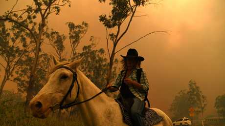 Rhonda Anderson evacuates herself and her horse to safety near Mount Larcom, Queensland, Wednesday, November 28, 2018. Fire conditions in the area are rated as potentially catastrophic with 140 fires burning around the state. (AAP Image/Dan Peled)