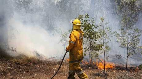 A firefighter works on a fire ground at Deepwater, north of Bundaberg. Picture: QFES via AP