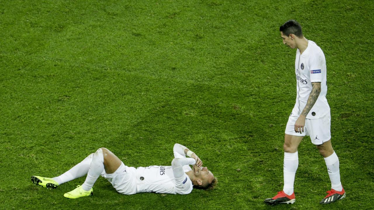 Paris Saint-Germain's Brazilian forward Neymar lies on the ground as Paris Saint-Germain's Argentine midfielder Angel Di Maria walks by during the UEFA Champions League Group C football match between Paris Saint-Germain (PSG) and Liverpool FC at the Parc des Princes stadium, in Paris, on November 28, 2018. (Photo by Geoffroy VAN DER HASSELT / AFP)