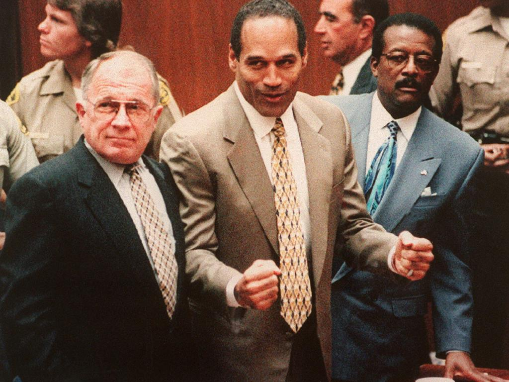 Defendant O.J. Simpson (C) cheers while standing with his lawyers F. Lee Bailey (L) and Johnnie Cochan Jr (R), after hearing the not guilty verdict in his criminal murder trial. Picture: Getty