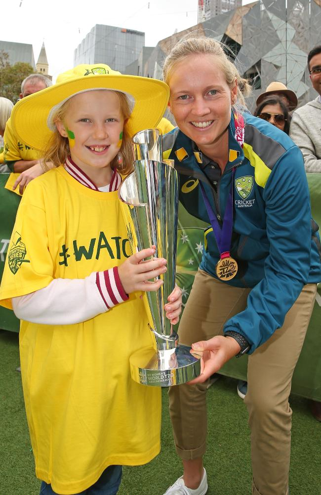 Skipper Meg Lanning shows off the trophy to a young fan.