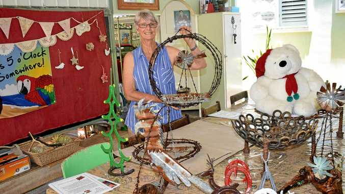 CHRISTMAS CHEER: Allison Close with a selection of interesting backyard art and other donated items which will be up for sale at this year's Bouldercombe Christmas Fair.