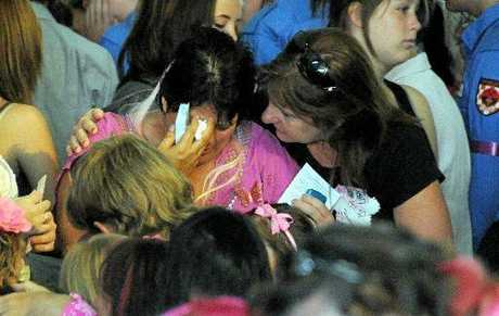 Tammy Bradey in pink is comforted by another mourner at the funeral of her son Jaxson yesterday.