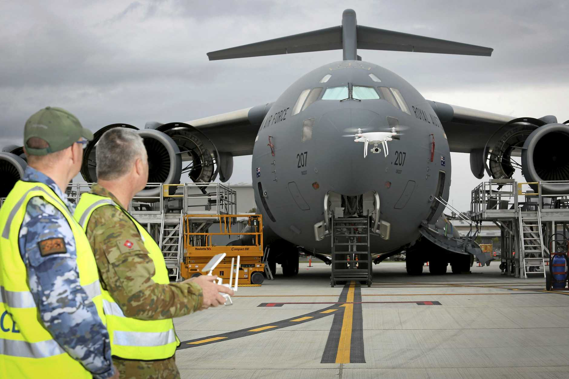 Australian Army soldier, Sergeant Andrew Whitelaw, from 16 Air Land Regiment and Corporal Kelvin Green, Aircraft Surface Finisher at Royal Australian Air Force No.36 Squadron, launch a drone to inspect the condition of paint on the upper surfaces of a C-17A Globemaster on the flightline at RAAF Base Amberley.