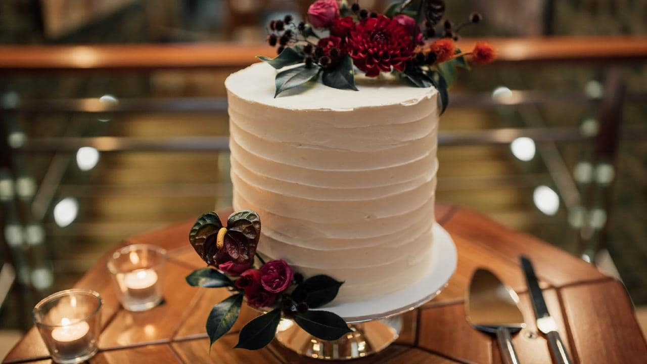 A vanilla butter cake with passionfruit ganache and buttercream icing, decorated with fresh flowers from Aurora Floral Studio, West End