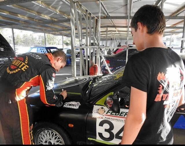 MEETING HERO: David Reynolds signs Kyle Evans' car after taking him on a ride around the track at Morgan Park.