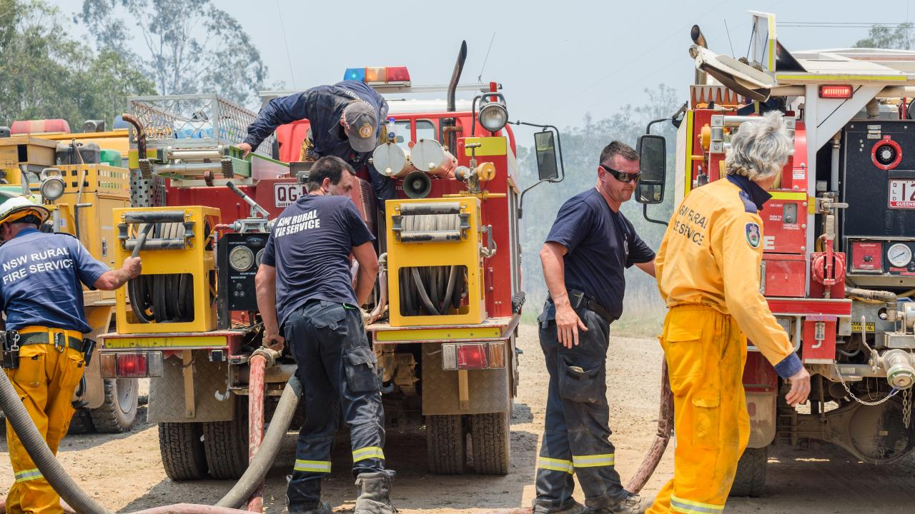 Firefighters refill their trucks at Captain Creek, north of Bundaberg yesterday. Picture: AAP Image/Paul Beutel