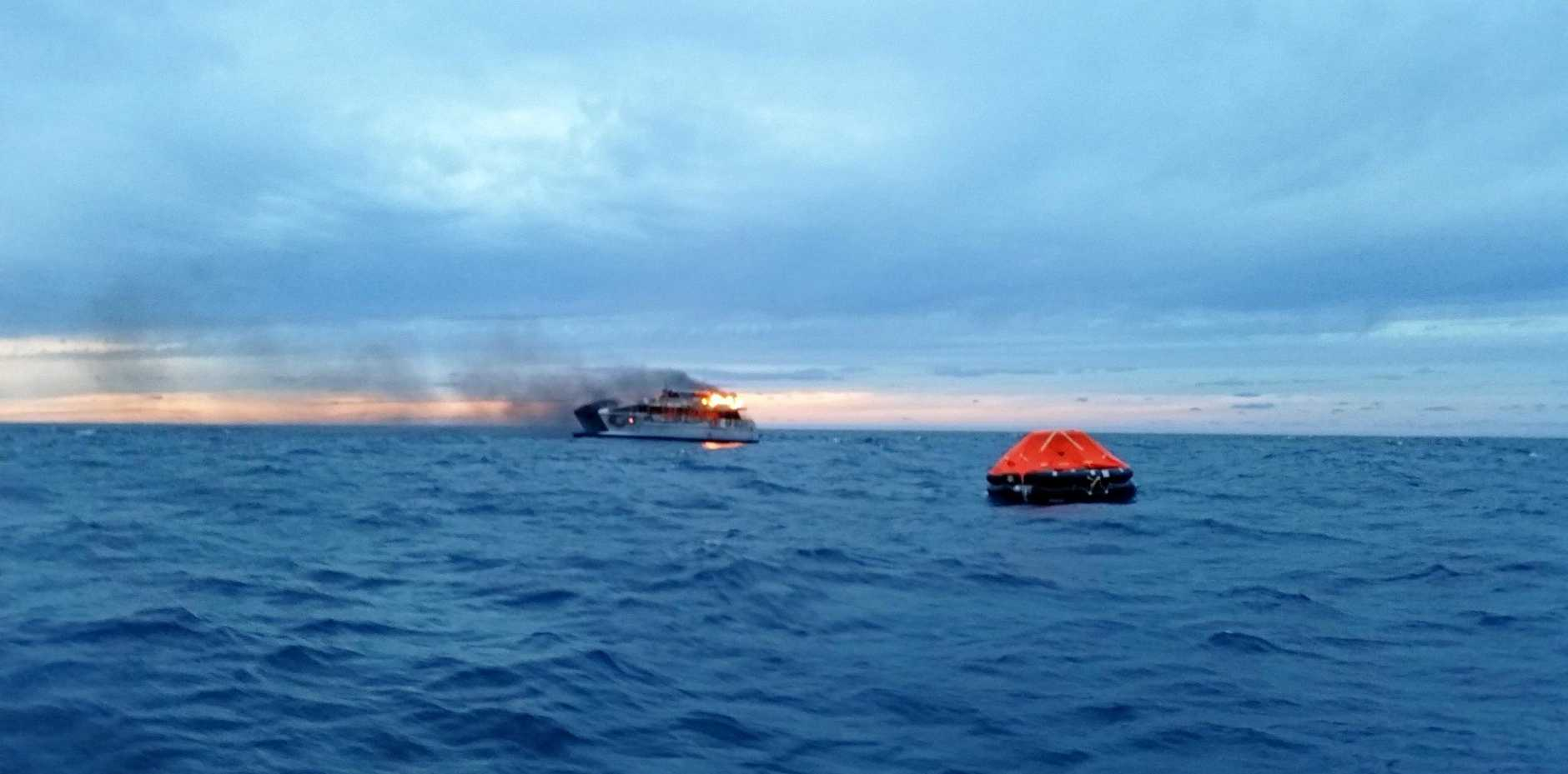 BOAT BLAZE: The Spirit of 1770 pictured at sunset on May 11 as it burnt to the waterline near Lady Musgrave. Inset: Emergency services cared for the passengers on baord.
