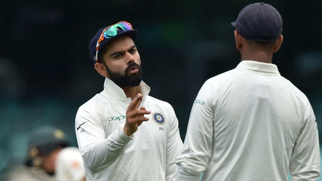 India's captain Virat Kohli (L) talks to Cheteshwa