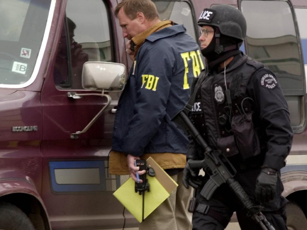 A police officer walks past an FBI agent looking into an abandoned van found behind a Colorado Springs restaurant on January 23, 2001, as officials searched for the last two gang members still at large. Picture: AP Photo/David Zalubowski