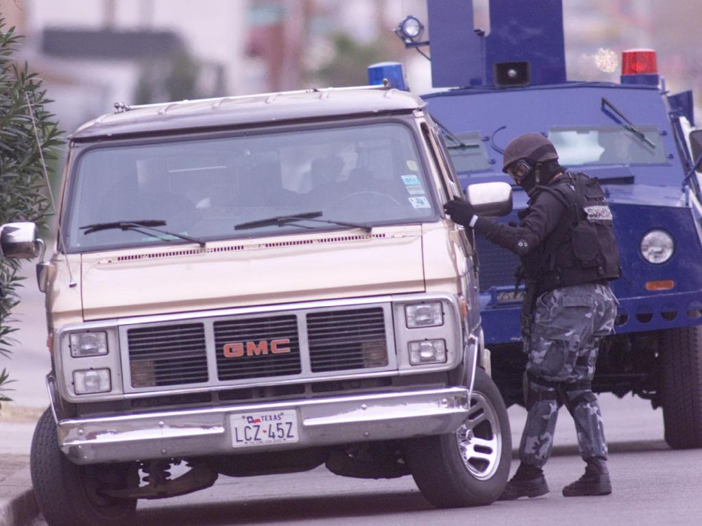 An El Paso County Sheriff's SWAT team member inspects a van matching the general description of one taken by Murphy and Newbury on January 22, 2001, in El Paso. Picture: AP Pic/El Paso Times, Victor Calzada