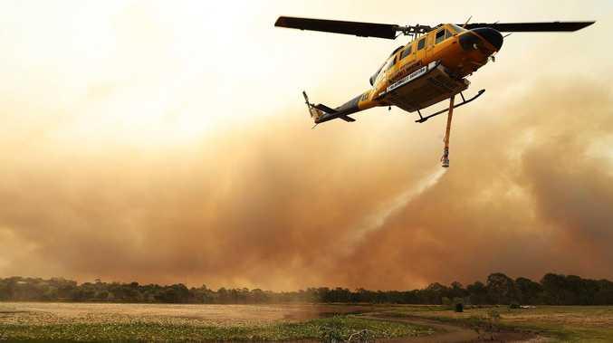 A firefighting helicopter picks up water from a prawn farm near Deepwater during last week's bushfire emergency. Picture: Lyndon Mechielsen/The Australian