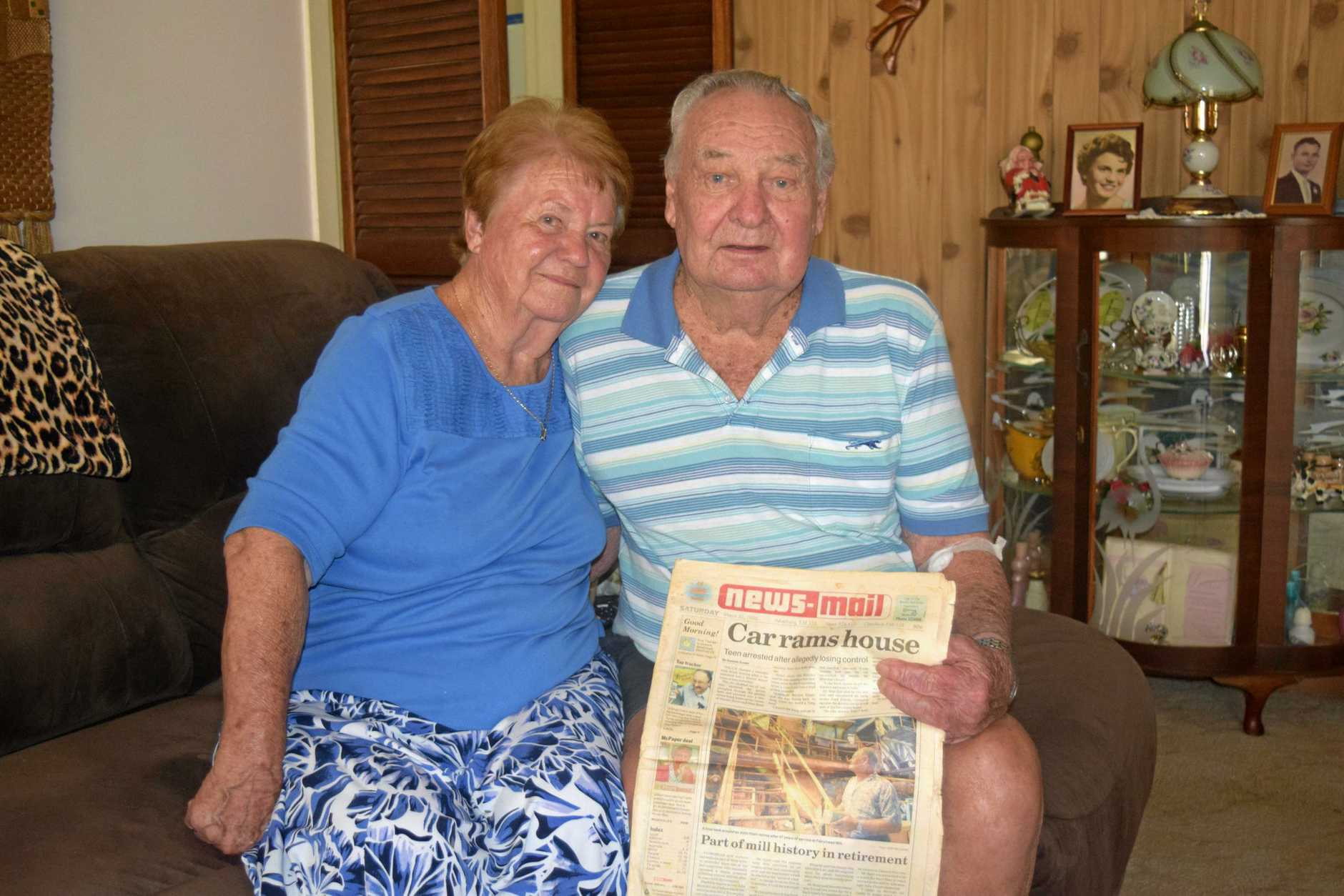John Hunt, 85, and wife Joan Hunt, 78, holding a 1996 copy of the NewsMail from when he was featured on the front page in honour of his retirement from the Fairymead Mill.